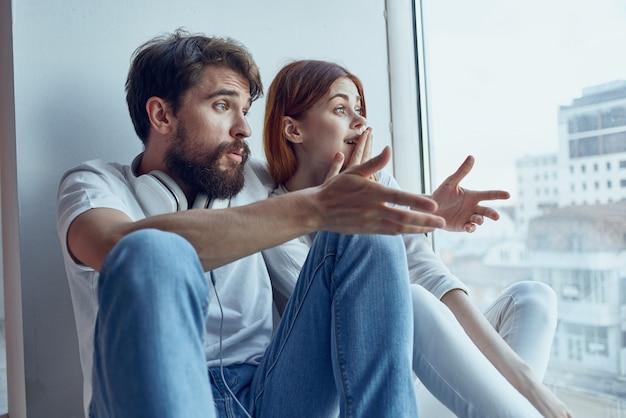 Jeune couple assis sur le rebord de la fenêtre près de la fenêtre de communication