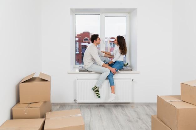 Jeune couple assis sur le rebord de la fenêtre profitant d'un nouvel appartement