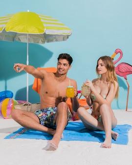 Jeune couple assis sur une serviette avec cocktail en studio