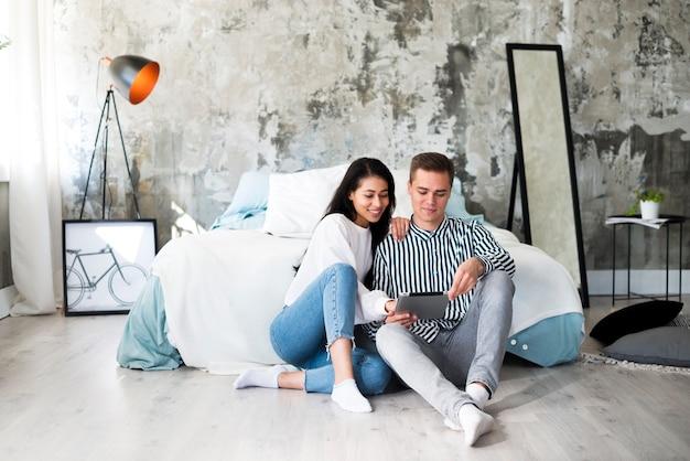 Jeune couple assis sur le sol et à l'aide de tablette