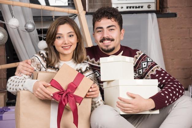 Jeune couple assis sur le sol avec des cadeaux de noël dans la salle des fêtes.