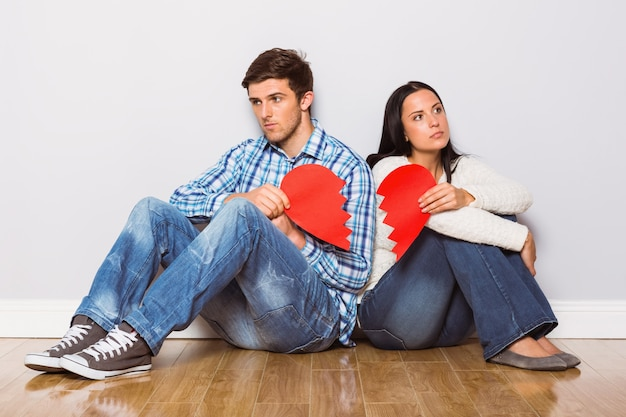 Jeune couple assis sur le sol avec cœur brisé