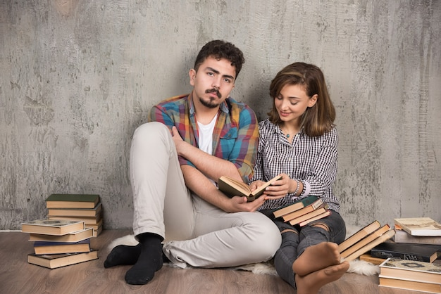 Jeune couple assis sur le sol et lisant un livre