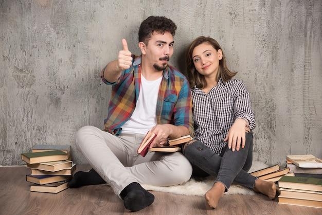 Jeune couple assis sur le sol avec des livres et abandonner les pouces vers le haut