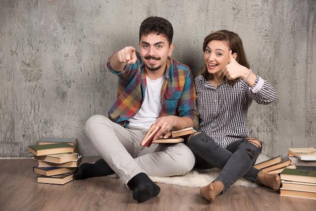 Jeune couple assis sur le sol avec des livres et pointant vers l'avant