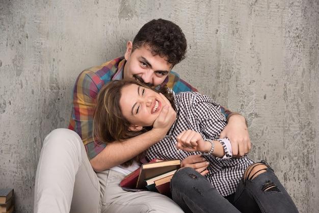 Jeune couple assis sur le sol avec des livres