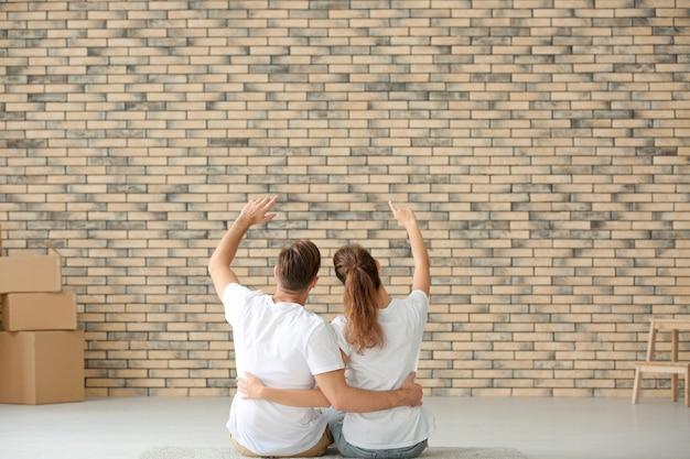 Jeune couple assis sur le sol à la nouvelle maison