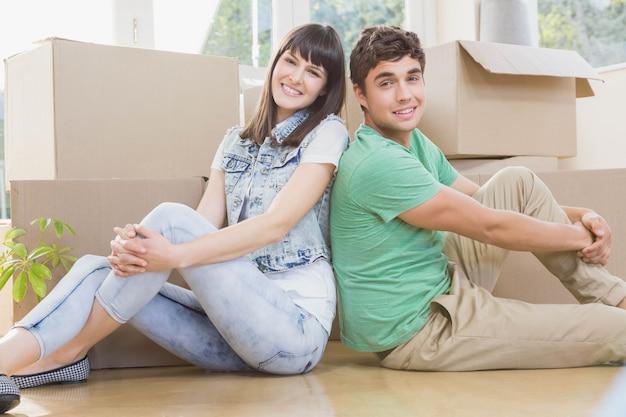 Jeune couple assis sur le sol et souriant dans leur nouvelle maison