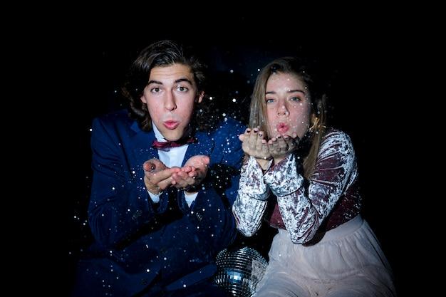 Jeune couple assis et souffle bisou sur la fête