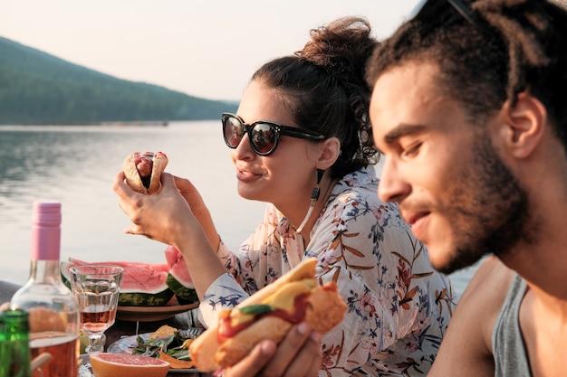 Jeune couple assis à la table de manger des hot-dogs sur la nature à l'extérieur