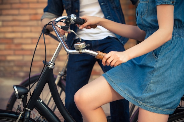 Jeune couple assis sur un vélo en face de la ville