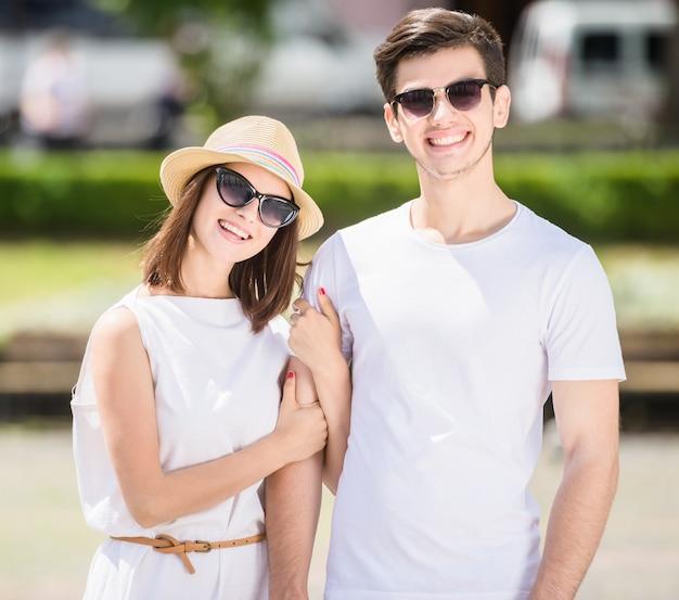 Jeune couple astucieux marchant le long de la rue un jour d'été.