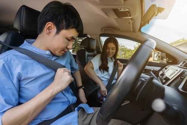 Jeune couple attachant la ceinture de sécurité avant de conduire une voiture.