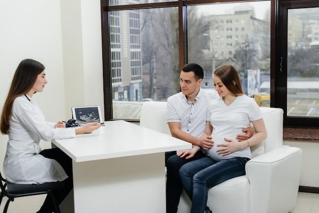 Un jeune couple attend un bébé pour consulter un gynécologue après une échographie. grossesse et soins de santé.