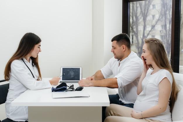 Un jeune couple attend un bébé pour consulter un gynécologue après une échographie.