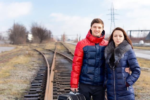 Jeune couple en attente sur la voie ferrée avec une valise debout bras dessus bras dessous en attendant l'arrivée du train pour commencer leurs vacances