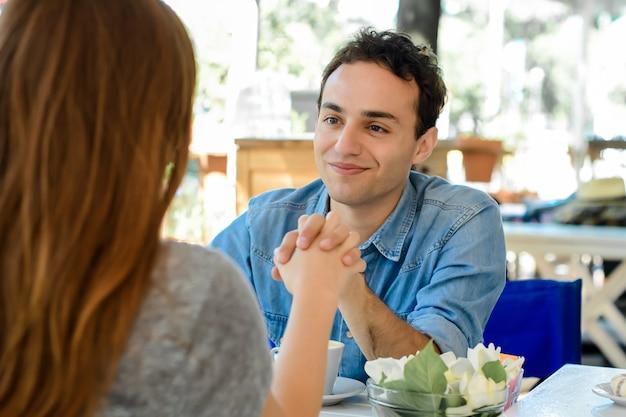 Jeune couple attrayant à date dans un café