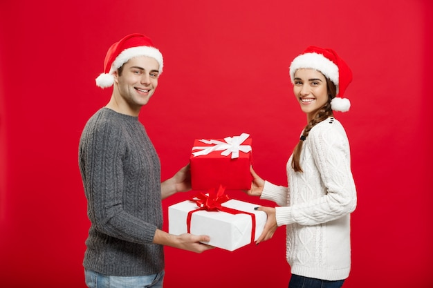 Jeune couple attrayant donnant des cadeaux les uns aux autres célébrant le jour de noël.