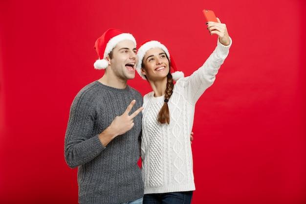 Jeune couple attrayant prenant un selfie par téléphone portable célébrant le jour de noël.