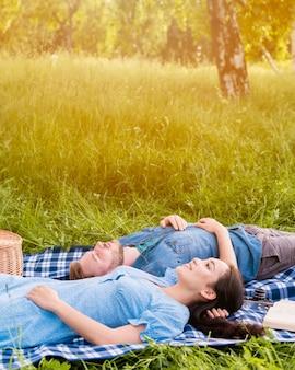 Jeune couple attrayant se détendre sur un pique-nique dans la nature