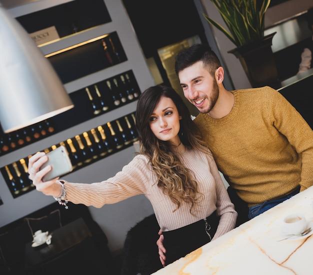 Jeune couple au bar prenant un selfie.