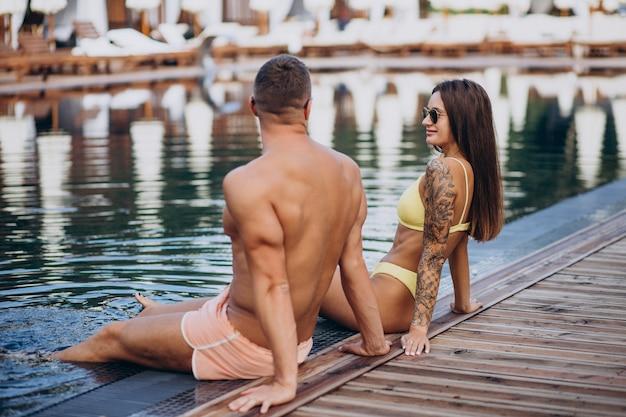 Jeune couple au bord de la piscine