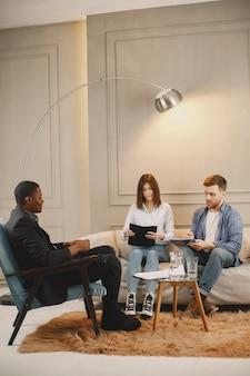 Jeune couple au cabinet psychologue. ils font des tests ou remplissent la couverture pour la thérapie.