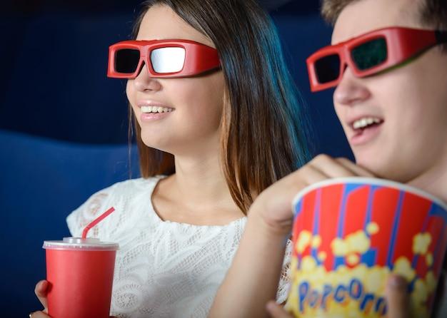 Jeune couple au cinéma en regardant un film avec pop-corn.