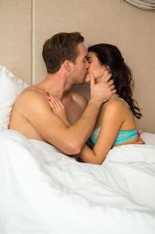 Jeune couple au lit s'embrasser.
