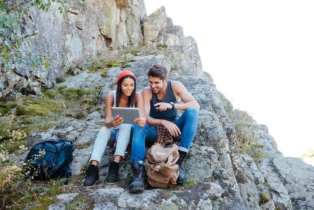 Jeune couple au repos et à l'aide d'un ordinateur tablette alors qu'il était assis sur une montagne rocheuse