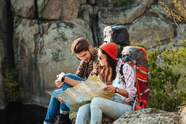 Jeune couple aventurier avec carte assis sur la pente regarde la carte