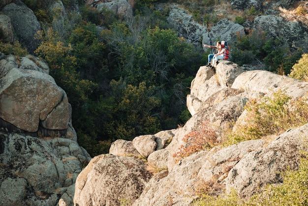 Jeune couple aventurier est assis sur un rocher