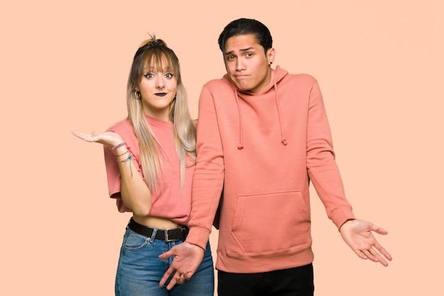 Jeune couple ayant des doutes en levant les mains et les épaules