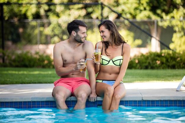 Jeune couple ayant du thé glacé au bord de la piscine par une journée ensoleillée