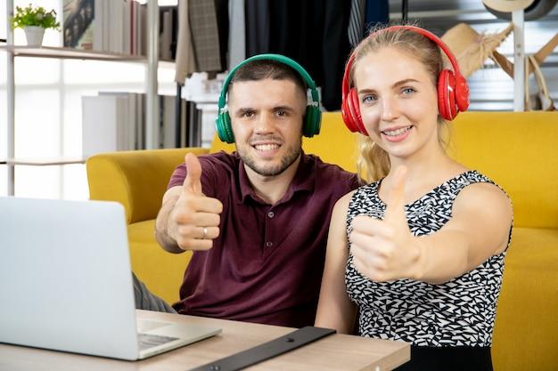 Jeune couple ayant un moment romantique et rire ensemble dans le salon tout en regardant un film sur ordinateur portable