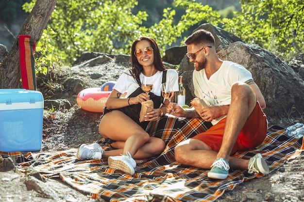 Jeune couple ayant pique-nique au bord de la rivière en journée ensoleillée. femme et homme, passer du temps sur la nature ensemble. s'amuser, manger, jouer et rire. concept de relation, amour, été, week-end.