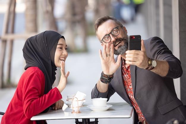 Jeune couple ayant romantique dans le restaurant assis à prendre des photos