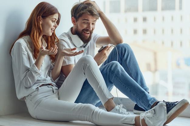 Un jeune couple bavardant près de la technologie de joie de romance de fenêtre