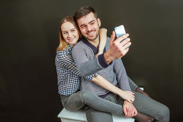 Jeune Couple De Bel Homme Barbu Et Femme Blonde Assise Sur Fond Noir Et Faisant Un Drôle De Selfie. Prise De Vue En Studio Photo Premium