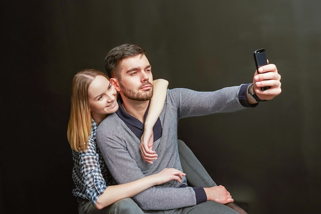 Jeune couple de bel homme barbu et femme blonde assise sur fond noir et faisant un drôle de selfie. prise de vue en studio