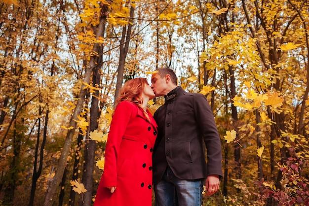 Jeune couple bisous dans la forêt d'automne parmi les arbres colorés
