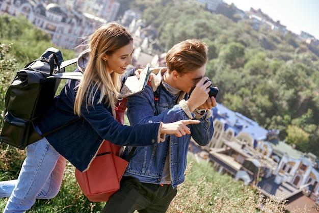 Un jeune couple de blogueurs de voyage essaie de faire une photo dans un endroit inconnu