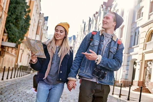 Un jeune couple de blogueurs de voyage essaie de naviguer par carte dans une ville inconnue