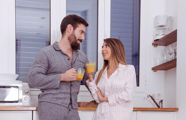 Jeune couple, boire jus, cuisine