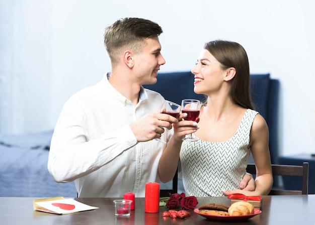 Jeune couple, boire vin, table