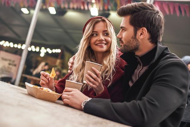 Un jeune couple boit du vin chaud avec des collations au marché de l'alimentation de rue