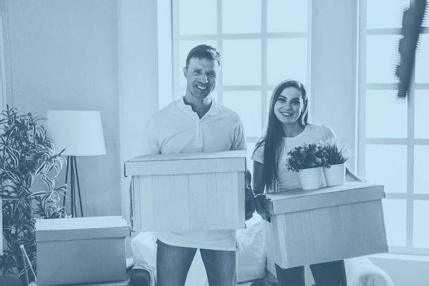 Jeune couple avec des boîtes en carton debout dans un nouvel appartement