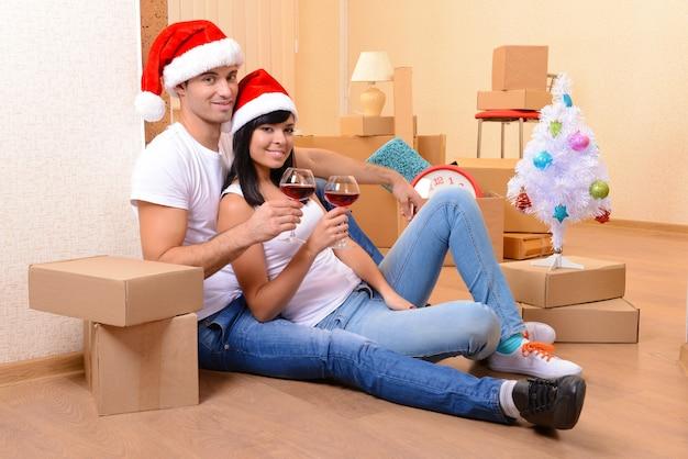 Jeune couple avec des boîtes dans une nouvelle maison célébrant le nouvel an