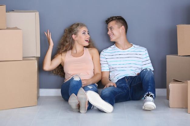 Jeune couple avec des boîtes de déménagement sur le sol dans la chambre à la nouvelle maison