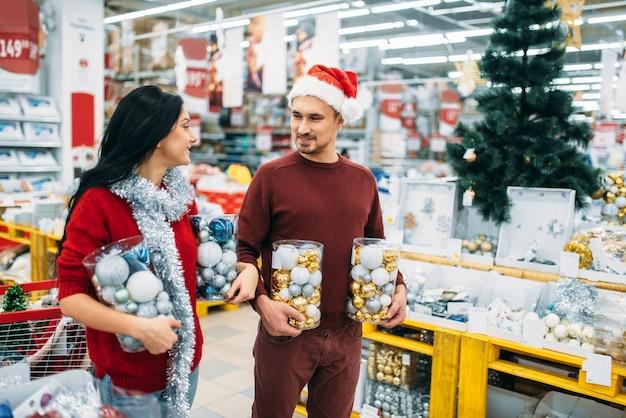 Jeune couple avec des boîtes pleines de boules de noël en boutique